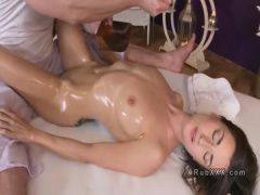 Masseur pours oil to redheads breasts