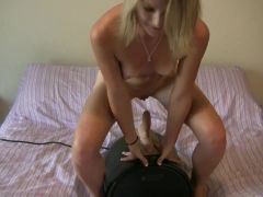 Young blonde rides a fuck machine in her bedroom