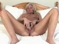 Mature cunt lips open wide as she plays with her pubes