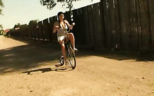 Girl in pigtails riding her bike naked
