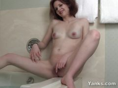 Redhead vixen playing with her pussy in bath tube.