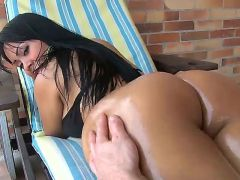 Paola demonstrates her lovely big ass, then lies on the couch and gets her ass cheeks covered with good portion of oil. The masseur slows down when he