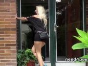 Blonde on heels pissing at a building entrance